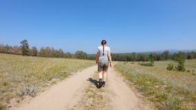 Young girl walking on a country road. Young girl with braid in shorts and t-shirt walking on a country road. Back view, gimbal shot stock video footage