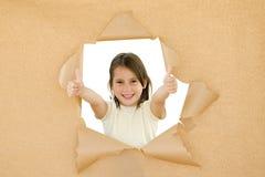 Young girl braking through. A paper Royalty Free Stock Photo