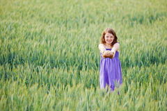 Young girl with bread in a wheatfield Royalty Free Stock Images