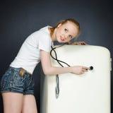 A young girl breaks the fridge Stock Photos