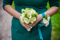 Young girl-bride or bridesmaid is holding a wedding bouquet. Bridesmaid is holding a wedding bouquet before church Stock Images