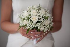 Young girl-bride or bridesmaid is holding a wedding bouquet. Bridesmaid in white is holding a wedding bouquet before church Stock Photography