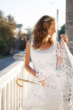 Young girl bride with decorative umbrella in the sunny city Stock Image