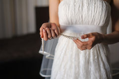 Young girl or bride holding a necklace of pearls. Bridal preparation, bride putting on pearls, focus on hands with necklace Stock Photos