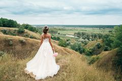 A young girl, the bride in a long wedding dress, is turned her back and stares into the distance to the river and a beautiful land Stock Photos