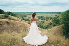 A young girl, the bride in a long wedding dress, is turned her back and stares into the distance to the river and a beautiful land Stock Photo