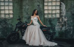 Young girl bride on a new man`s motorcycle. royalty free stock image