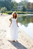 Young girl bride walk barefoot the sunny coast of the river Stock Image