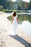 Young girl bride walk the sunny coast of the river Royalty Free Stock Images