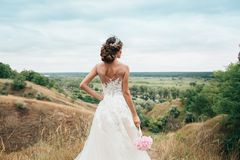 A young girl, the bride in a wedding dress, is turned her back and staring into the distance on the river and a beautiful landscap Stock Photography