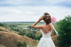 A young girl, the bride in a wedding dress, is turned her back and staring into the distance on the river and a beautiful landscap Stock Image