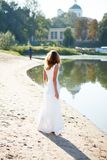 Young girl bride in a white dress on the sunny coast of the river Stock Images
