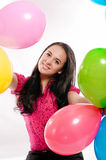 Young girl with bright colored balloons on a white Royalty Free Stock Photo