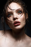 A young girl with bright creative makeup and perfect skin. Beautiful model with wet hair on face Royalty Free Stock Images