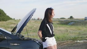 Young girl with a broken car with open hood