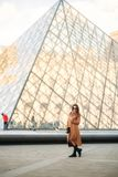A young girl in a brown coat and scarf stands on the background of the Louvre. Autumn is sunny weather, tourists. Royalty Free Stock Images