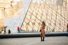 A young girl in a brown coat and scarf stands on the background of the Louvre. Autumn is sunny weather, tourists. Royalty Free Stock Photos