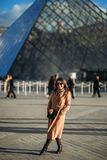 A young girl in a brown coat and scarf stands on the background of the Louvre. Autumn is sunny weather, tourists. Stock Photos