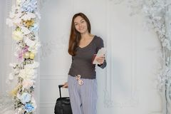 A young girl in a brown jacket with tickets and a passport in her hands looks at the camera, smiles, carries a suitcase royalty free stock image