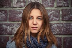 Young girl with brown straight hair next to brick wall. Stylish teen female model in blue scarf Stock Photos