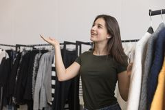 Young girl, brunette, in a clothing store, smiling. stock photo