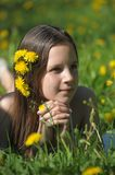 The young girl the brunette lies on a glade with dandelions stock images