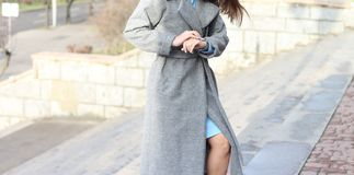 Young girl, brunette, looks at the watch, wristwatch, checks the time, walks the stairs, hurries to a meeting. One in a gray coat and a blue dress, autumn stock photos