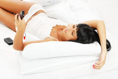 Young girl - brunette on white bed Stock Images