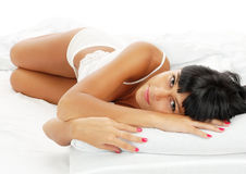 Young girl - brunette on white bed Royalty Free Stock Photos