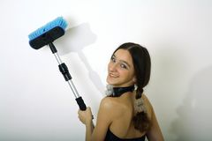 Young girl with brush. Young smiling girl teenager use brush for washing or painting white wall stock photos