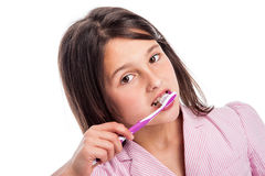 Young Girl Brushing Teeth. Pretty young girl brushing her teeth. Isolated on stduio white background royalty free stock images
