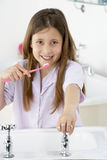 Young Girl Brushing Teeth at Sink Royalty Free Stock Photography