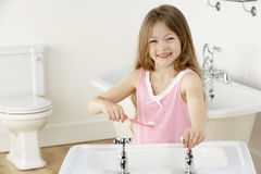 Young Girl Brushing Teeth at Sink Royalty Free Stock Photos