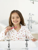Young Girl Brushing Teeth at Sink Royalty Free Stock Images