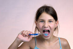 Young girl brushing teeth. And smiling royalty free stock image
