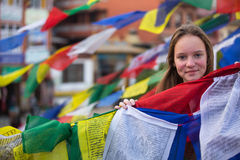 Young girl and Buddhist prayer flags flying. Travel. Stock Photo
