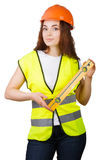 The young girl the builder in a helmet and a vest with level in hands Stock Photos