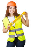 The young girl the builder in a helmet and a vest with level in hands Stock Images