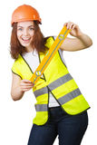 The young girl the builder in a helmet and a vest with level in hands Royalty Free Stock Image