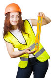 The young girl the builder in a helmet and a vest with level in hands Stock Photo