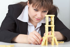 Young girl builds tower of dominoes Royalty Free Stock Images