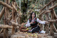 Young girl with bulgarian costume sitting on the ground with basket with apples Royalty Free Stock Photos
