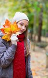 Young girl with bunch of autumn leaves Stock Images