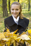 Young girl with a bunch of gold leaves Stock Photography