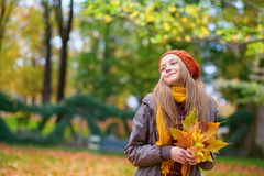 Young girl with bunch of leaves on a fall day Royalty Free Stock Photo