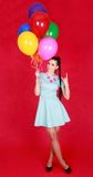 Young girl with bunch of many bright balloons