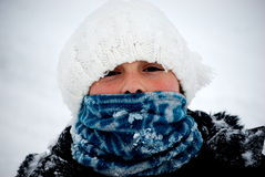 Young girl bundled up outside in snow. A headshot of a young preteen girl bundled up with a hat and scarf on a snowy cold winter day during a blizzard royalty free stock photo