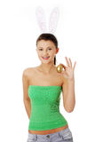 Young girl with bunny ears holding golden egg Royalty Free Stock Photos