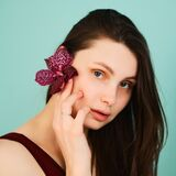 Young girl with a burgundy flower near her face on a turquoise background