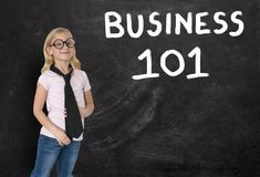 Young Girl, Businesswoman, Business 101, Chalkboard, Sales, Marketing. A young businesswoman girl stands in front of a chalkboard with BUSINESS 101 written on it Stock Image